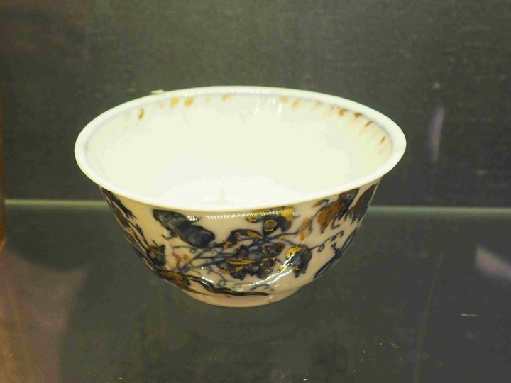 small cup is displayed with thin edges and blue and golden butterflies and flowers