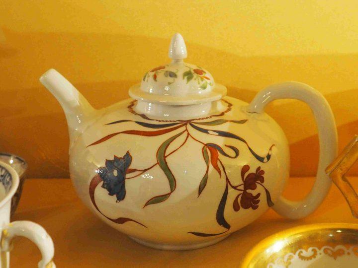 Teekanne mit rundem Körper, mit roten, grünen und blauen Blumen und langen Blättern