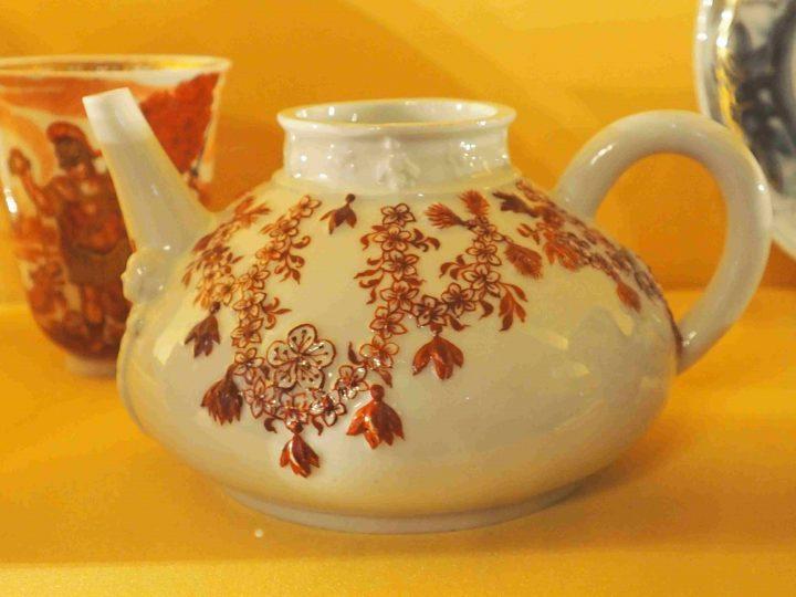 Teekanne mit Ghirlanden von roten Pflaumeblüten und Quasten