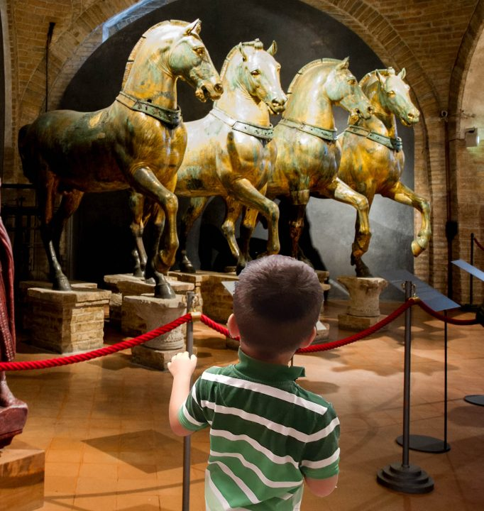 A young boy admiring the four horses in St. Mark's Basilica