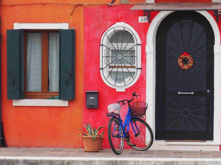 bicycle leaning against a coloured house