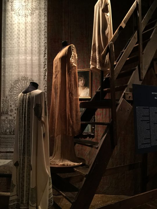 "photo 10: clothes displayed on Mariano's staircase with knossos veil in the background in a lovely setup by Palazzo Fortuny in 2016. The name of the veil is a homage to the archaeological findings in Crete during the early 1900s, which were a source of great inspiration for our artist. He was charmed by the ""modernity"" of Minoan decorations, which he in fact represented multiple times"