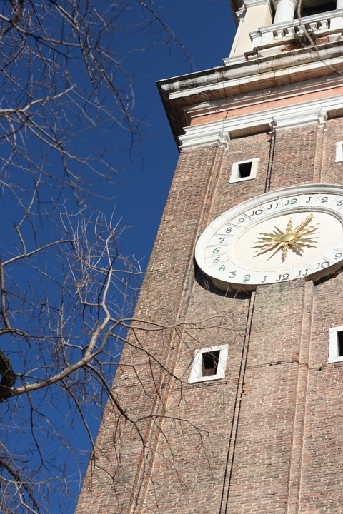 The bell tower and its beautiful dial of the church of Santi Apostoli, Venice