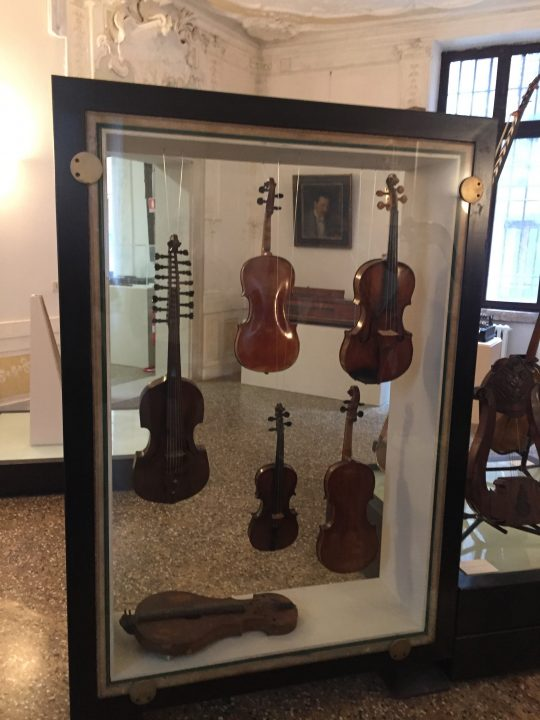 photo 13) identifiable in the display case: the viola d'amore on the left with its 7+7 tuning pegs that adjust and tune the strings. There are two violas at the top and two violins at the bottom with a vielle resting on the base of the case
