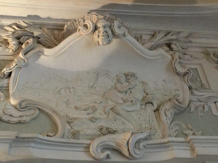 photo 4) l'un des quatre éléments, l'eau, représentée par Neptune, le dieu de la mer qui la déverse d'un vase, et par son inséparable compagnon, le dauphin, ici avec la queue de trident