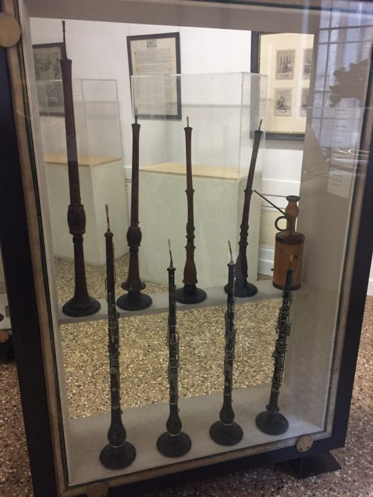 photo 31) this display case contains: two bombards (top left), two oboe d'amore and a rackett. In the bottom left, there are a cor anglais and three oboes. Bombards are Renaissance instruments with a double reed and part of the oboe family. Those in the Museum are two copies: one is a soprano and the other a (contr)alto